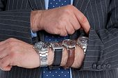 Businessman with four wrist watches checking the time. Good image for time related themes.