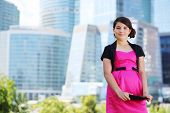 foto of bolero  - Smiling girl in pink dress with tablet pc stands near skyscrapers - JPG
