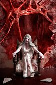 stock photo of fine art portrait  - Halloween fine art portrait of a beautiful young woman dressed as dark vampire in bloody white dress seated at the entrance to hell - JPG
