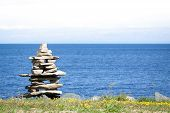image of caribou  - Inukshuk in front of the blue ocean - JPG