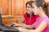 stock photo of preteen  - Young latin girl and her beautiful mother working on a computer and smiling - JPG