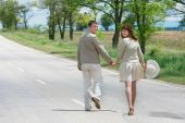 stock photo of walking away  - happy young couple walking by rural road - JPG