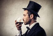 stock photo of cylinder  - elegant man with cylinder drinking a glass of red wine - JPG