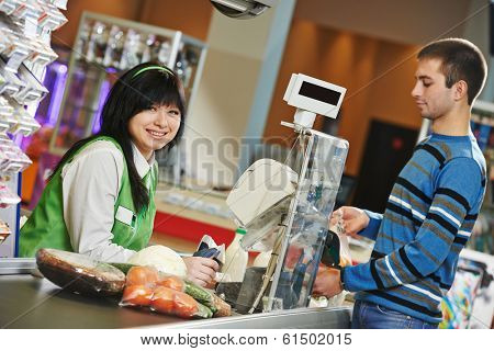 Customer buying food at supermarket and making check out with cashdesk worker in store