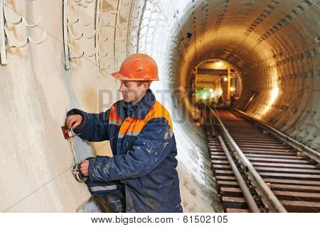 Tuneller worker installing fixture in underground subway metro construction site