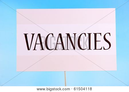 Nameplate with inscription Vacancies on bright background