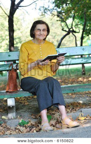 Senior Woman Reading Book Autdoors