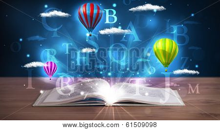 Open book with glowing fantasy abstract clouds and balloons on wood deck