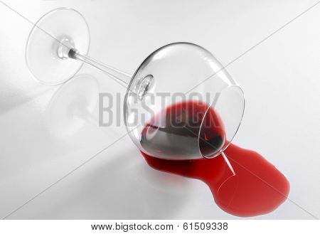 Overturned glass of wine isolated on white