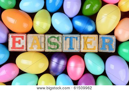 The word Easter spelled out in childrens toy blocks surrounded by a group of colorful plastic eggs. Horizontal format on a rustic wood background filling the frame.