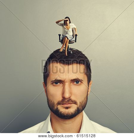 serious woman sitting on the man and looking at something