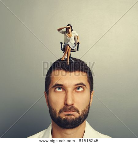 small serious woman peering into the distance and sitting on the stupid man over grey background