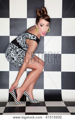 Attractive surprised young woman wearing high heels on checkered background,  fashion concept