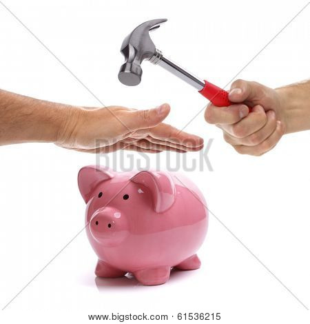 Hand with hammer about to smash piggy bank to get at savings being protected by another hand concept for protecting your assets, financial help and insurance