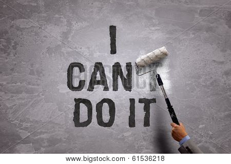 Changing the word can't to can by painting over and erasing part of it with a paint roller on a concrete wall in the phrase i can do it