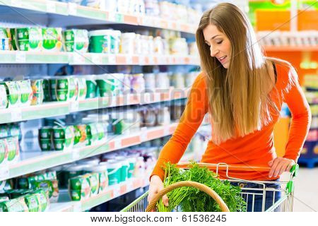 Young woman with shopping cart in supermarket looking for groceries