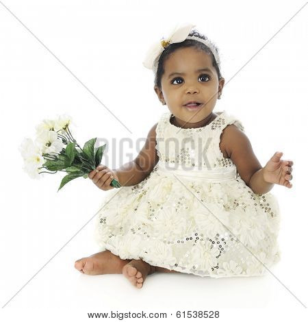 A beautiful baby girl dressed up and barefoot happily holding a small bouquet of flowers.  On a white background.