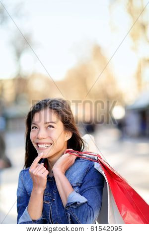 Shopping woman thinking looking up outdoors. Shopper girl holding shopping bags up excited outside on walking street. Mixed race Asian Caucasian female model cheerful on La Rambla street Barcelona.
