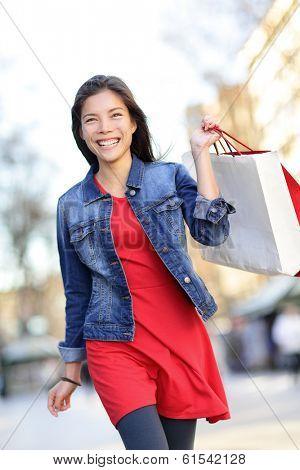 Shopper - woman shopping outside holding shopping bags walking outdoors smiling wearing denim jacket. Beautiful mixed race Asian Caucasian girl in her 20s.