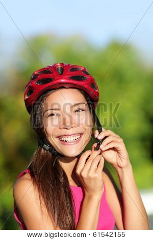 Biking helmet - woman putting bicycle helmet outside. Asian girl on bike, close up of helmet and face. Beautiful mixed race Caucasian Asian female outside.