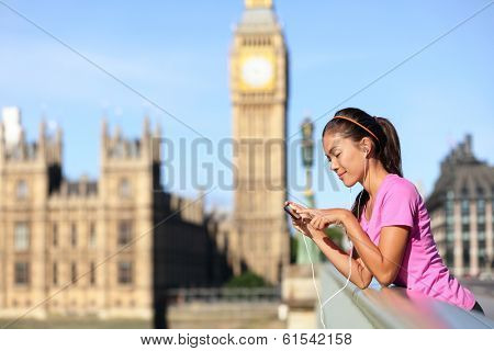 London lifestyle woman runner listening to music on smart phone near Big Ben. Female running girl resting after training in city. Fitness girl smiling happy on Westminster Bridge, London, England, UK.