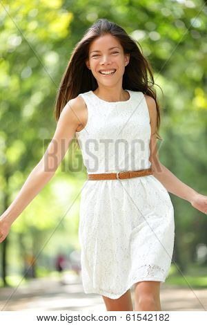 Happy Asian woman running in summer / spring park joyful and smiling in white sundress around trees. Beautiful fresh multiracial Asian Caucasian girl female model in her 20s outside.