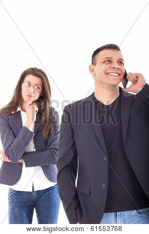 Upset Jealous Woman Looking At Her Man Chatting On The Phone