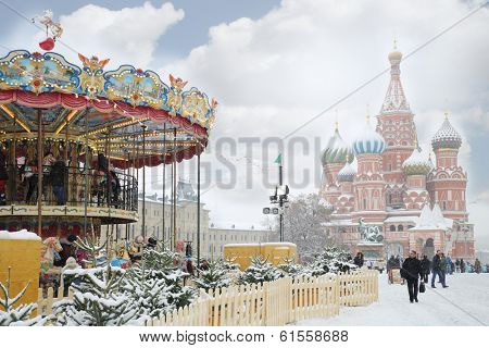 MOSCOW, RUSSIA - DEC 8, 2013: Carousel and St. Basil cathedral during Christmas fair (area of fair is about 2 thousand square meters).