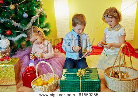 Three children sit in room under christmas tree among gift boxes untie ribbons on gift sweets