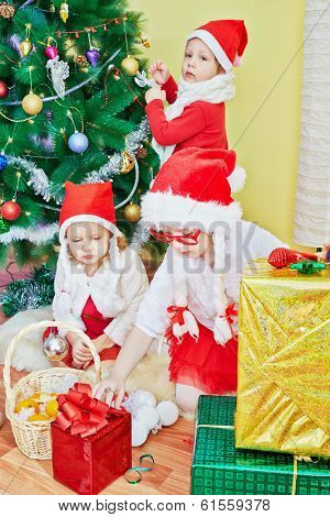 Two little girls in santa caps with strings in form of plaits examine gift boxes, boy decorates christmas tree, focus on girl in red glasses