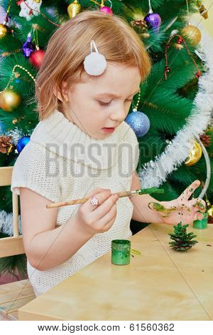 Little girl paints revealed pine-cone with green gouache sitting at wooden table