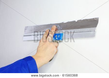 Hand of worker in blue clothes working by applicator in new apartment