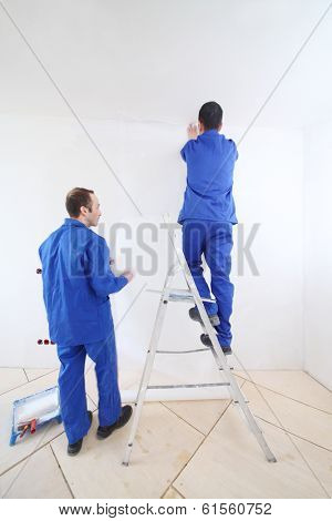Two workers in blue clothes on ladder paste paint fiberglass in new apartment