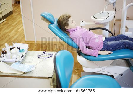 Girl in pink lies on dental chair in office and waits for doctor