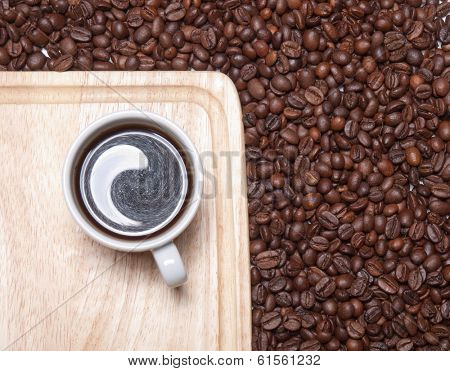A cup of coffe on breadboard with coffee grains