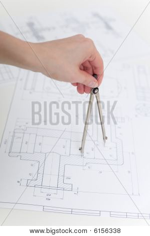 Hand Holds Metal Compasses Against Drawings