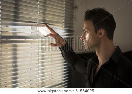 Profile Of Young Man Peeking Through Venetian Blinds