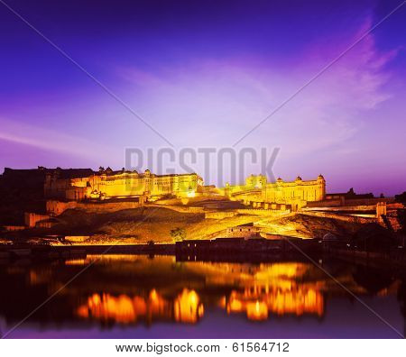 Vintage retro hipster style travel image of Amer Fort (Amber Fort) illuminated at night - one of principal attractions in Jaipur, Rajastan, India refelcting in Maota lake in twilight