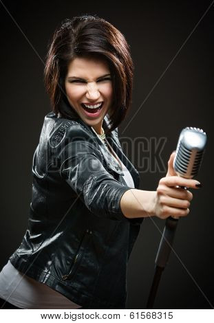 Half-length portrait of female rock musician wearing black jacket and handing mike on grey background. Concept of music and rave