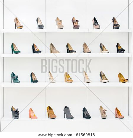 Showcase with female shoes placing in a row in the modern shopping center