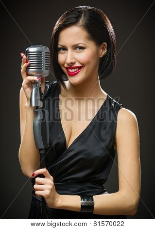Half-length portrait of female musician wearing black evening dress and keeping microphone on grey background. Concept of music and retro fashion