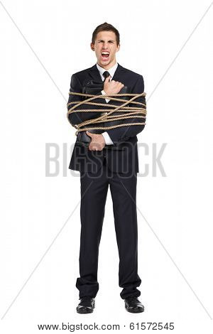 Full-length portrait of businessman screaming and handing briefcase who tied with the rope, isolated on white. Concept of slavery and violence