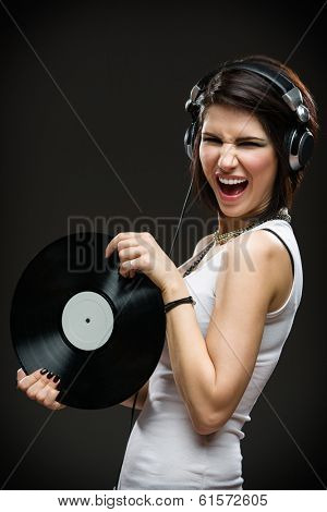 Half-length portrait of teenager with earphones and record in hands on grey background. Concept of rock music and arts