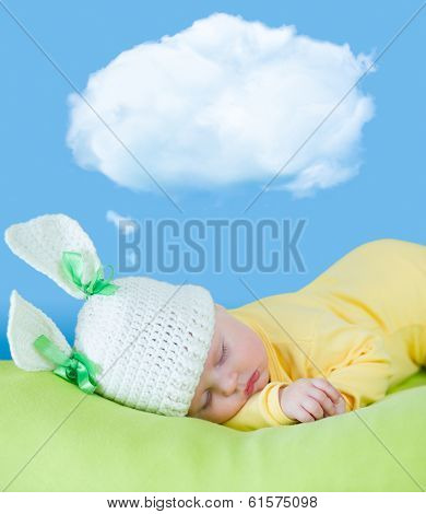 sleeping baby closeup portrait in hare or rabbit hat with dream cloud