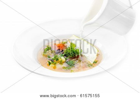 Fish Minestrone Pouring The Bouillon From The White Pitcher On White Background