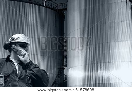 oil and gas engineer with giant industrial fuel tanks