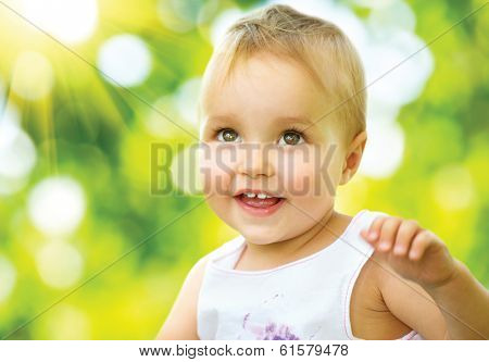 Little Baby Girl Portrait outdoor. Cute Child over nature background. Smiling adorable one year old baby. Sunny day