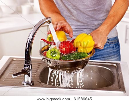 Happy man washing fruit at kitchen.