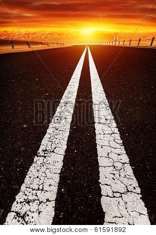 Long highway, road on sunset, red dramatic cloudy sky, two white line on dark asphalt, speed highway along desert,  freedom and travel concept