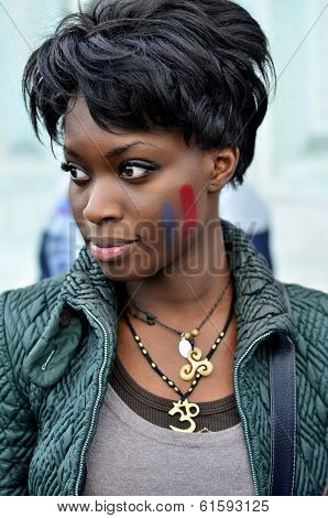 Beautiful black woman with french flag painted on her cheek